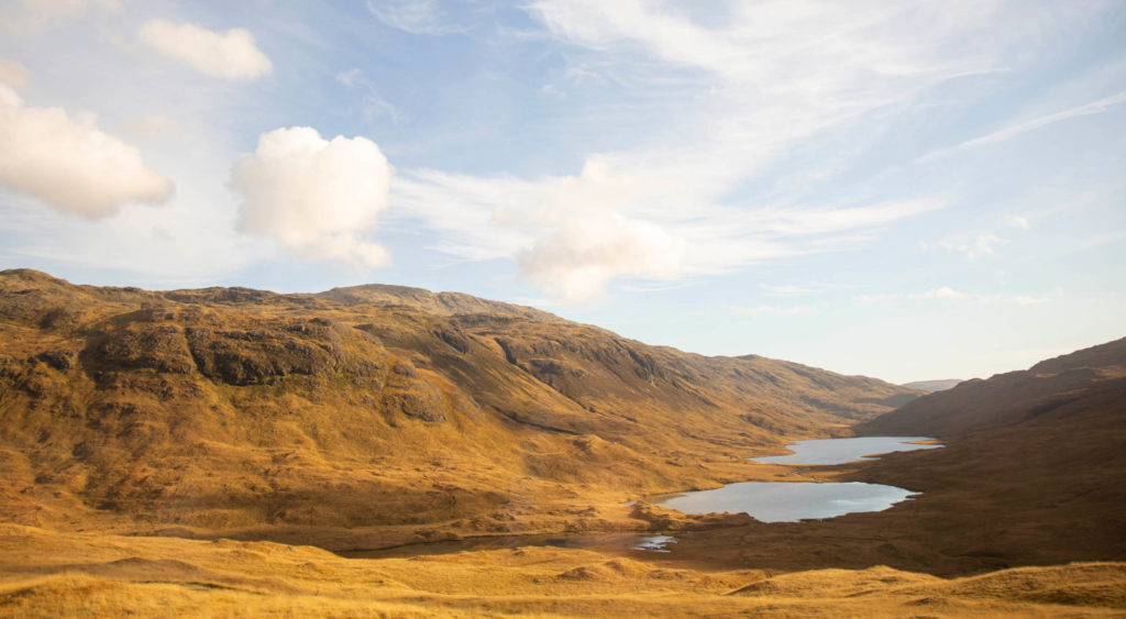 Three lochs against sandy mountain landscape and blue sky