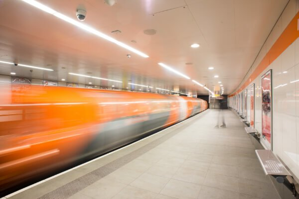 orange Glasgow subway train pulling in at stop