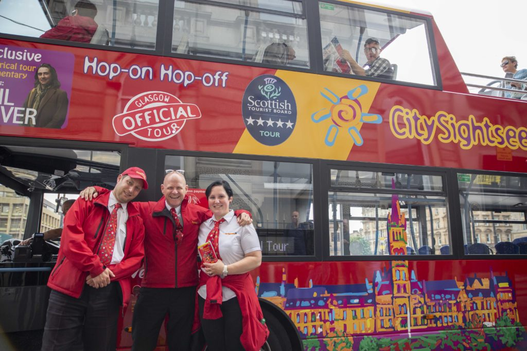 Two men and a woman who work for City Sightseeing Glasgow standing together beside a tour bus smiling