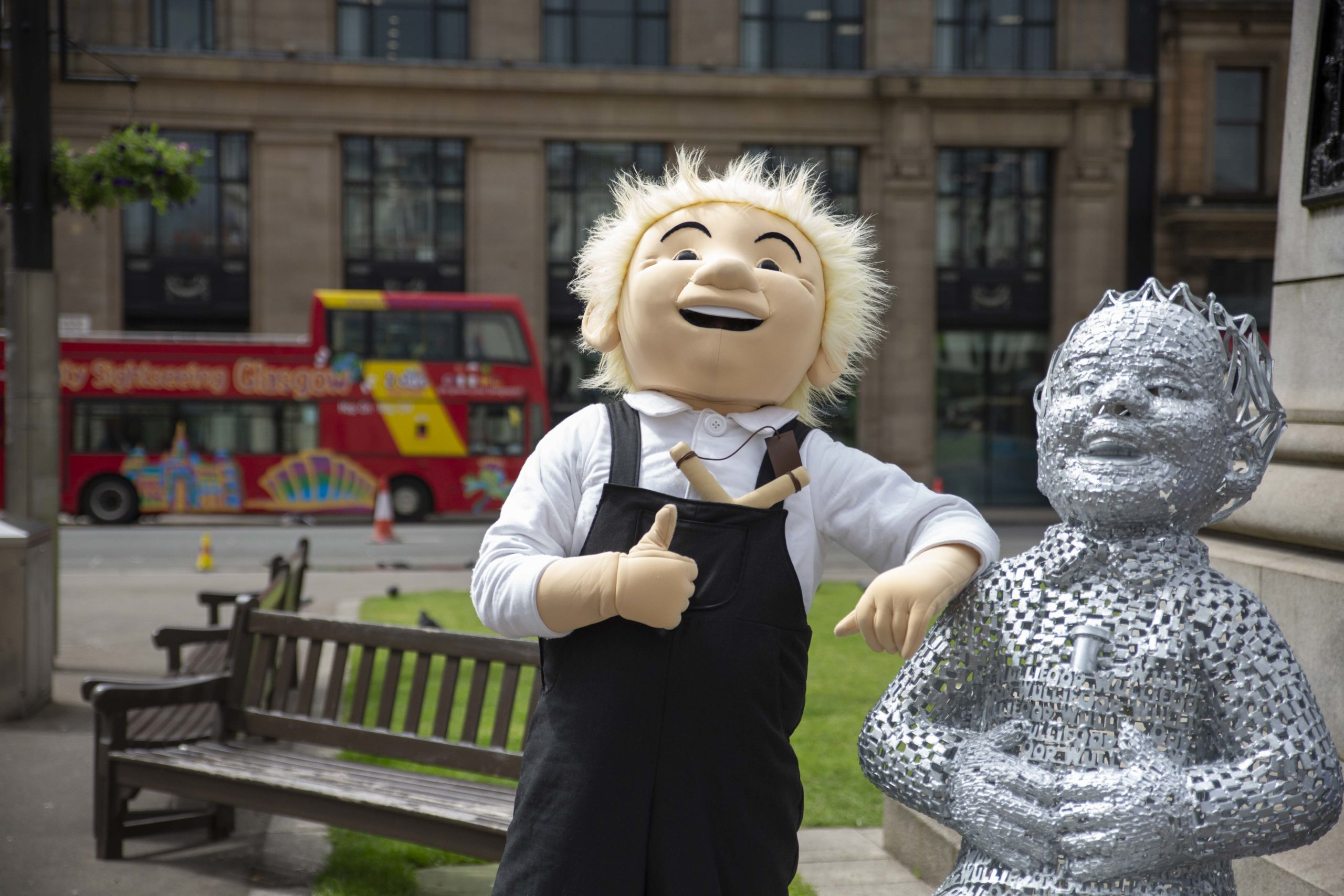 man in oor wullie suit posing next to silver oor wullie statue
