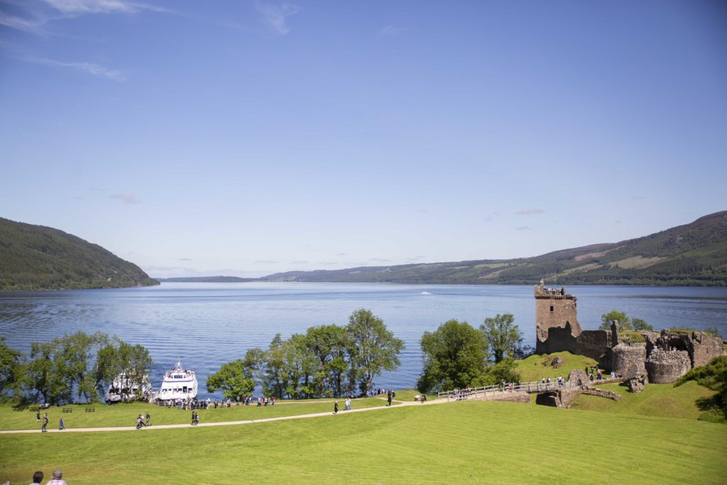 view out to loch ness with grass in the foreground, water in the background and ancient castle ruin in the middle