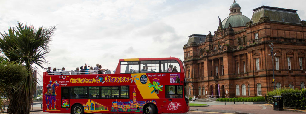 red open top bus outside Victorian building