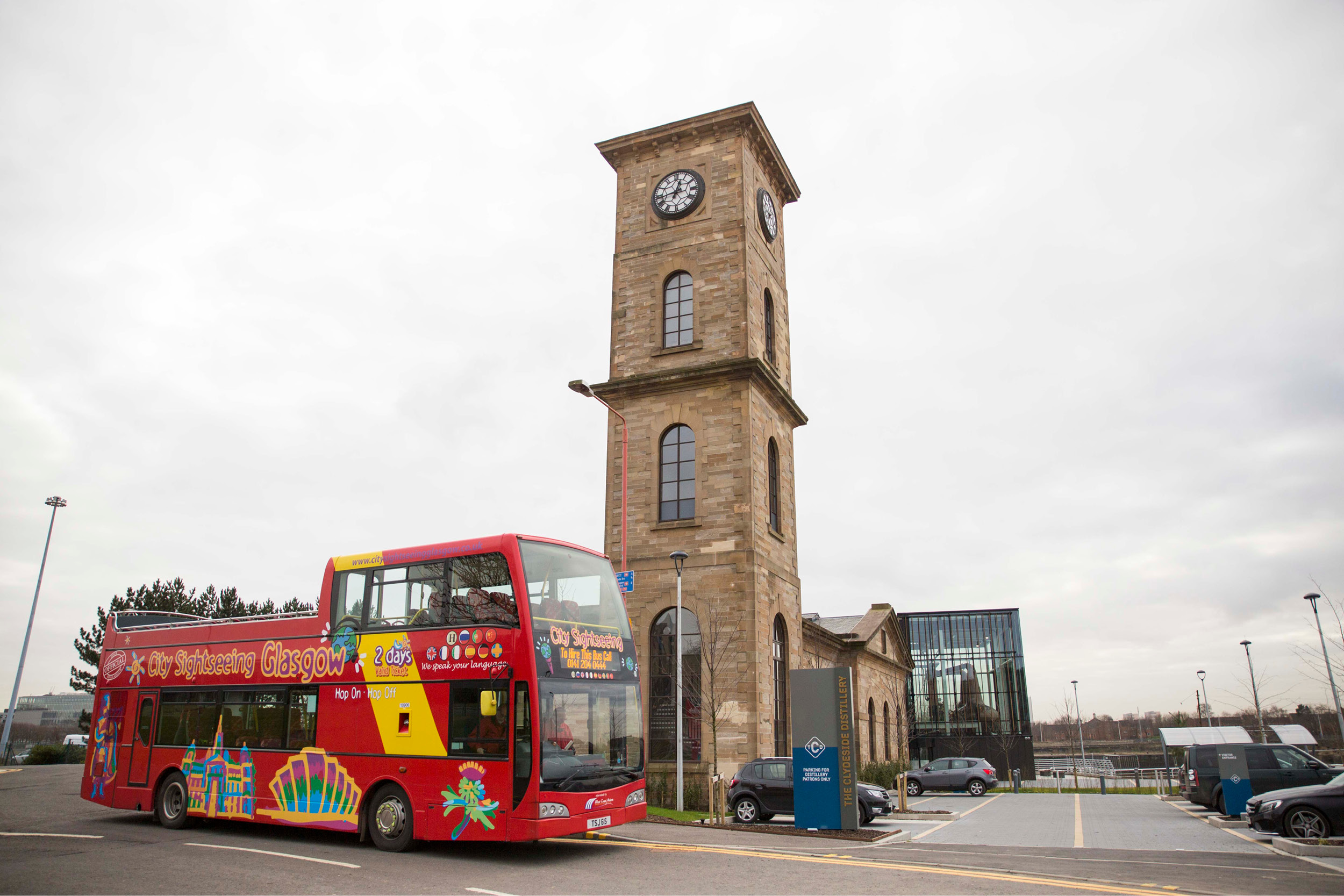 red double decker bus outside old tower building