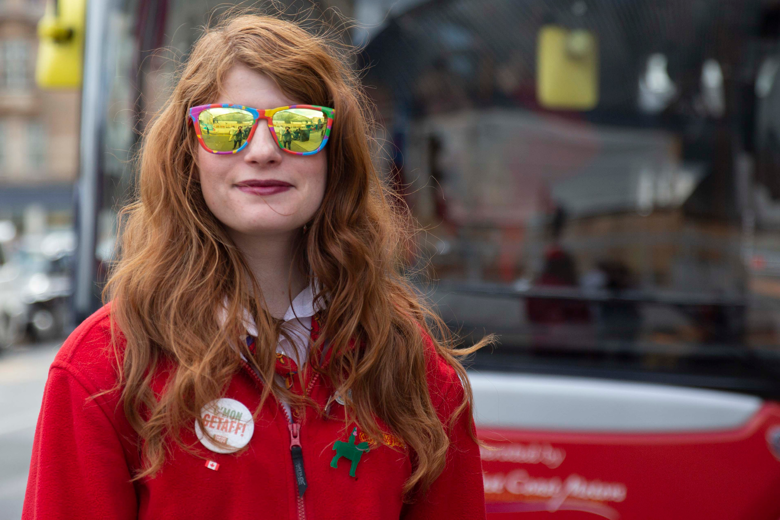 girl with red hair and red fleece wearing sunglasses and smiling
